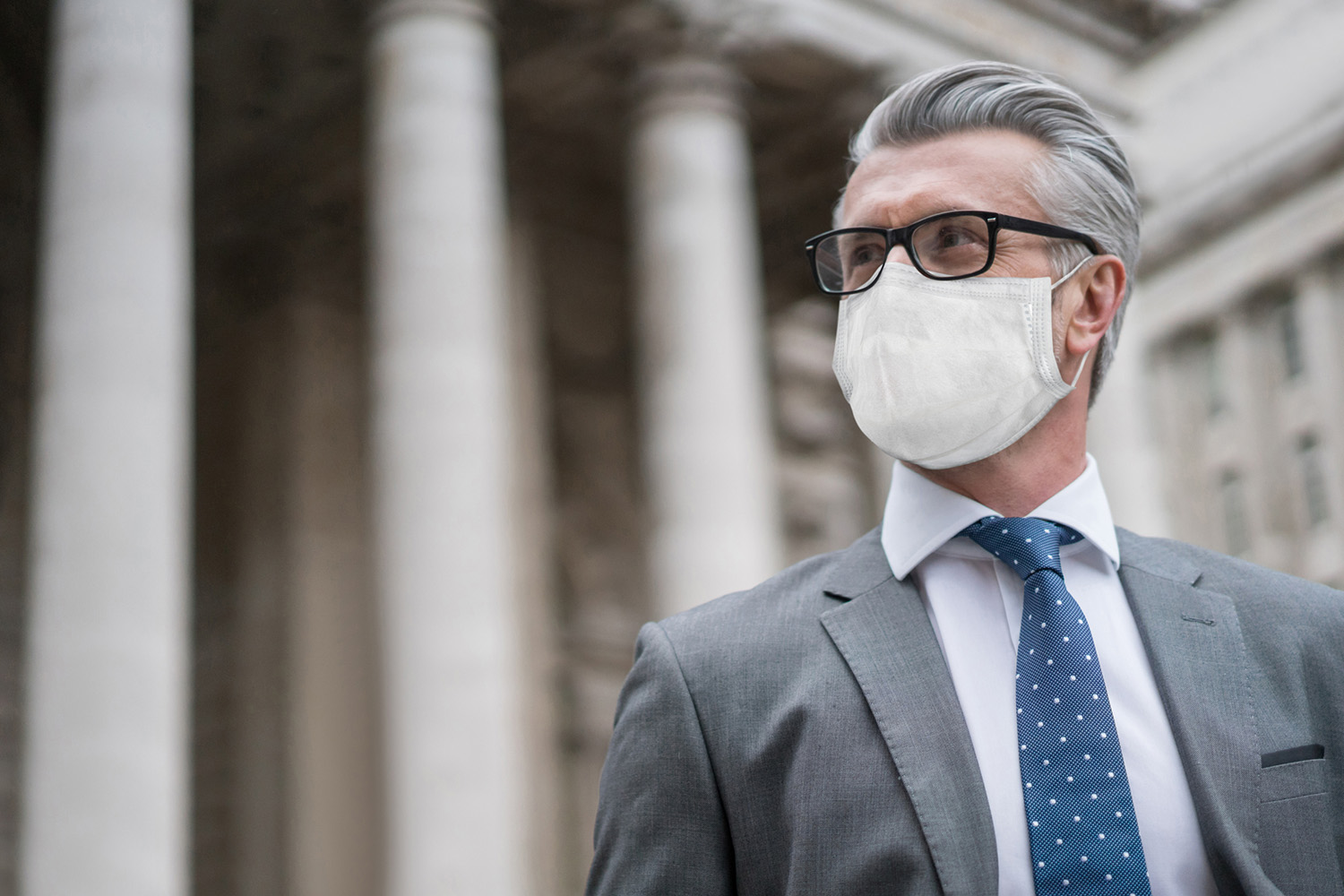 Portrait of a successful business man on the street wearing a facemask to avoid COVID-19 – Pandemic concepts